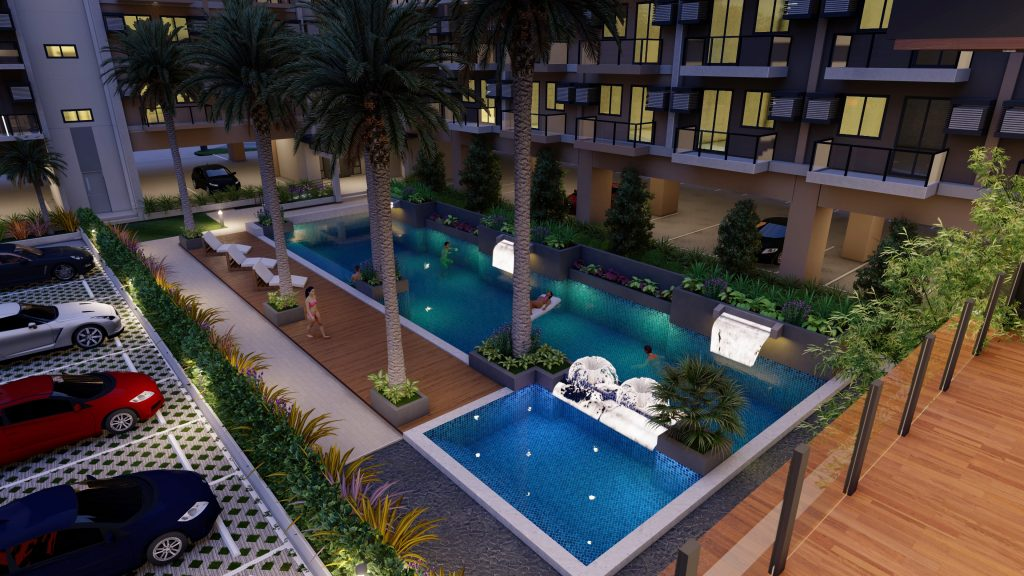 condo for sale in Las Piñas City swimming pool perspective at night with car parking spaces and greenery