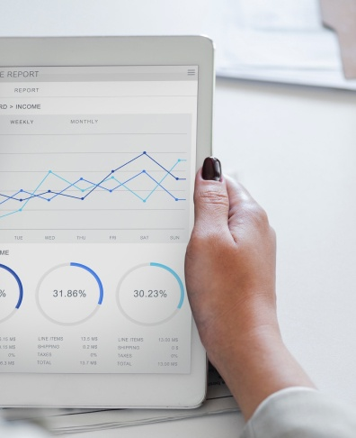 a hand holding a tablet with graphs and data
