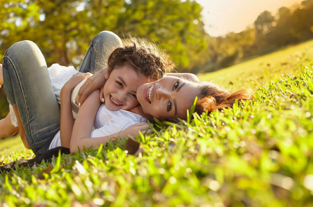 mom and child lying on the grass smiling at the camera in one sunny afternoon
