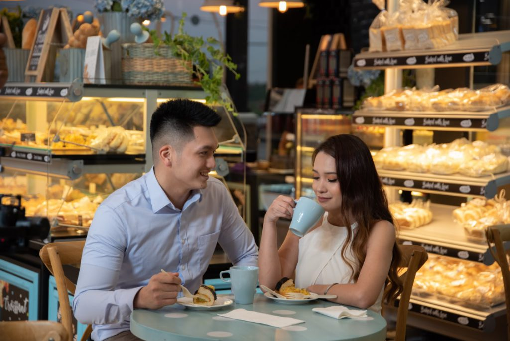 boy and girl drinking coffee in a bakeshop while sitting and talking on a table