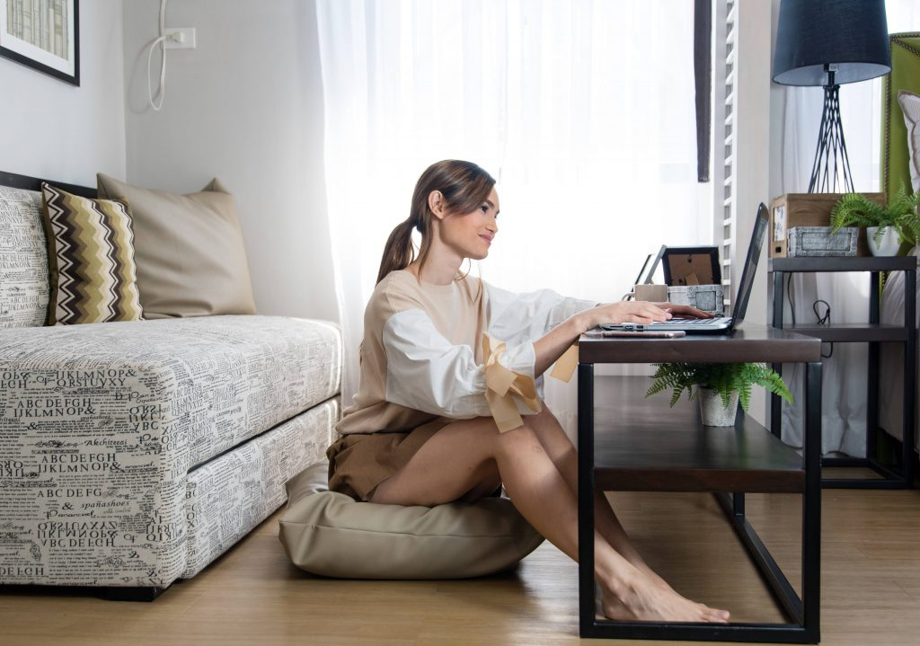 girl sitting on a pillow on the floor while using her laptop in her condo living room