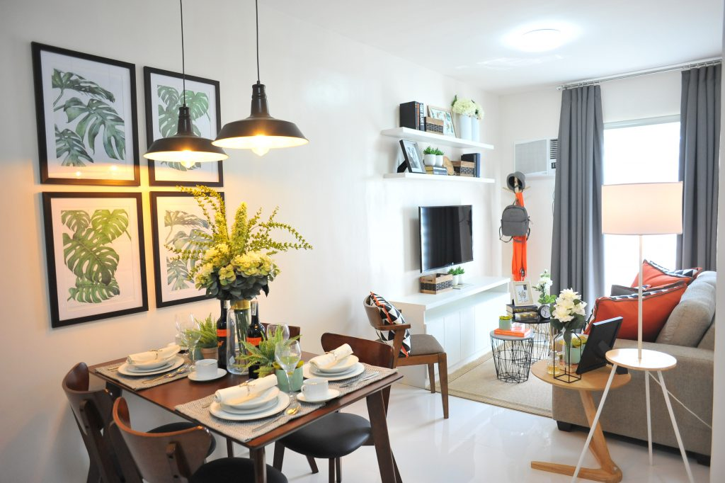 Condo unit room with plants in living room and dining table