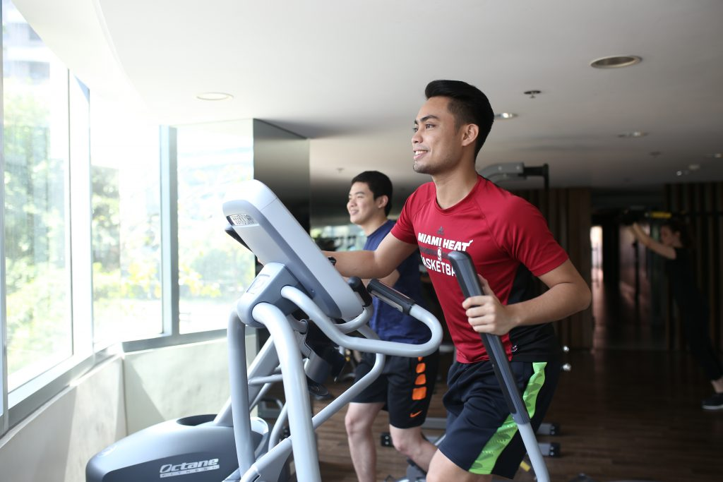 2 smiling boys exercising using gym equipment in a fitness gym of a condo for sale COHO by Vista Land real estate development