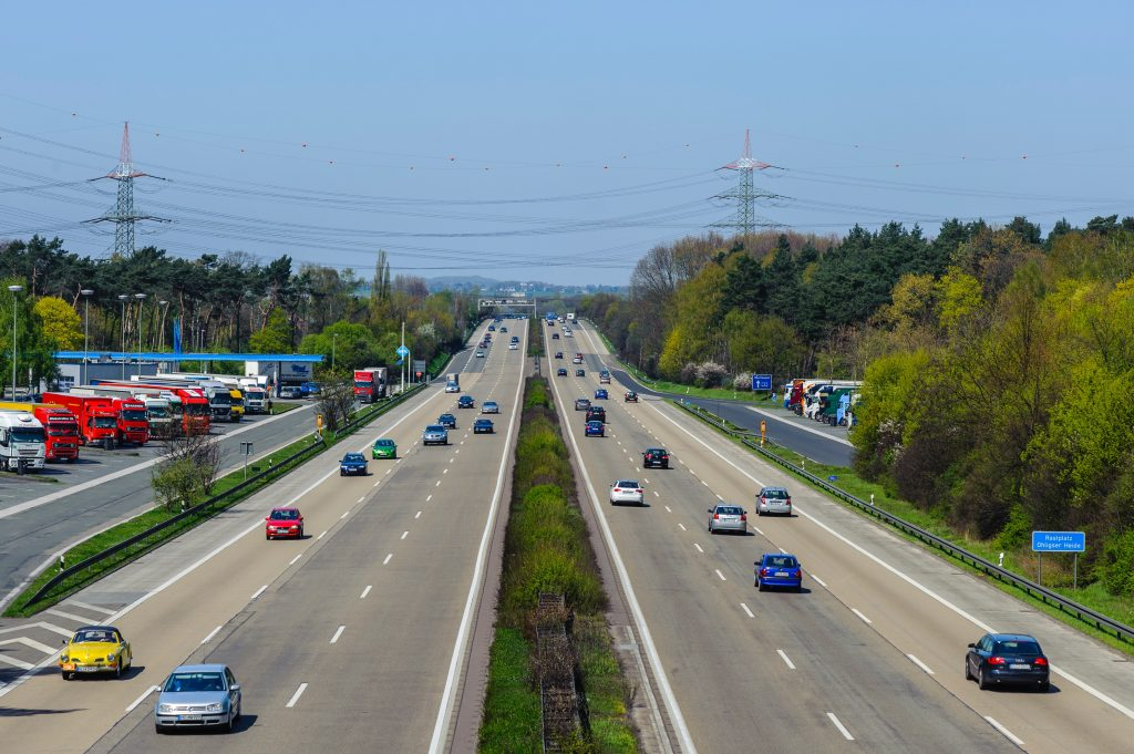 cars driving on highway with greenery and parked cars