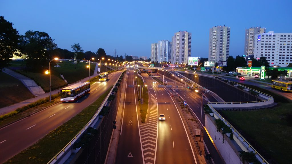 highway and roads with cars and tall condo developments in the background with blue sky