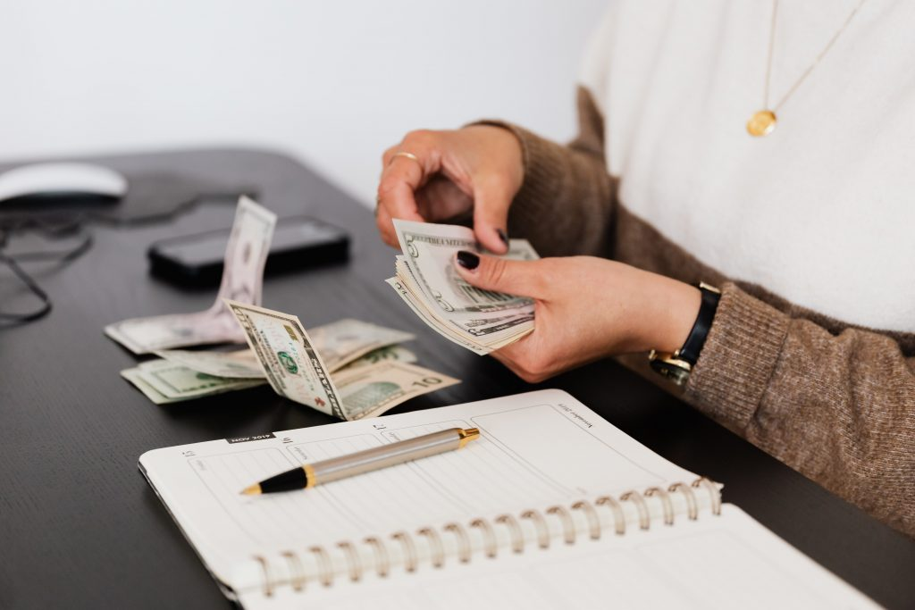 person holding money in hand and notebook and pen on a black table