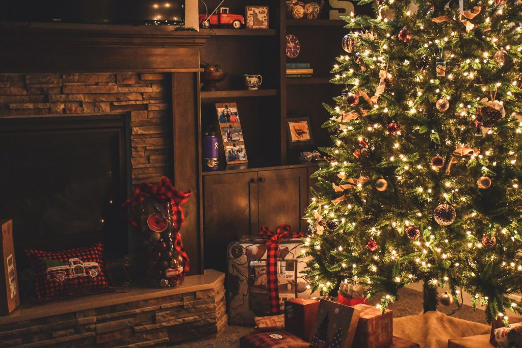 Christmas tree with lights and gifts in condo living room