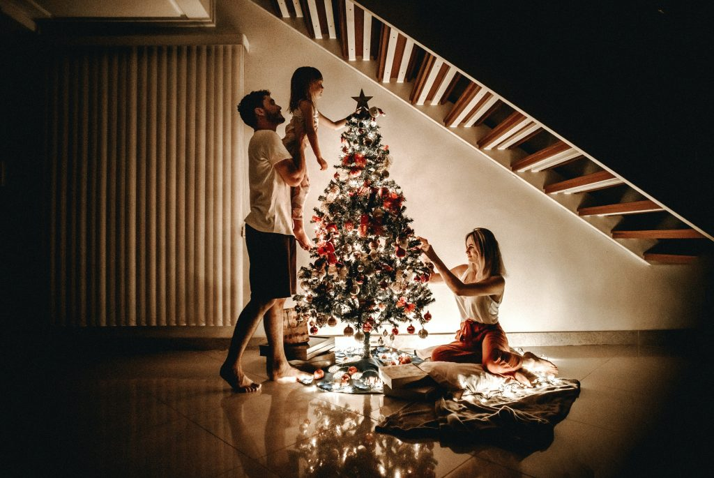 A family of 3 setting up the christmas tree and christmas lights in their condo living room