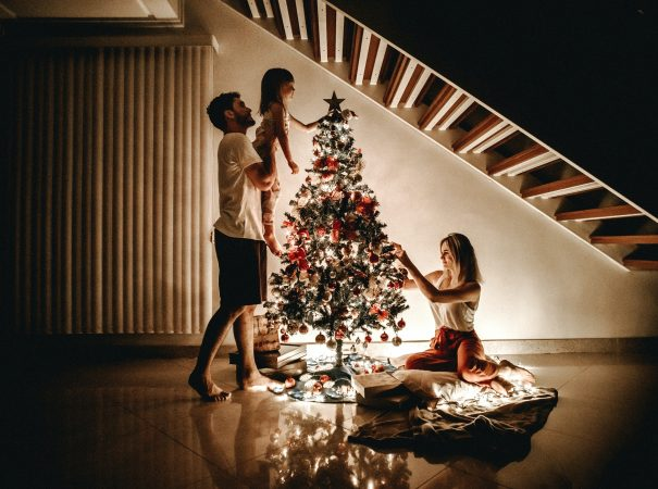A family of 3 decorating the christmas tree with christmas lights in their condo living room