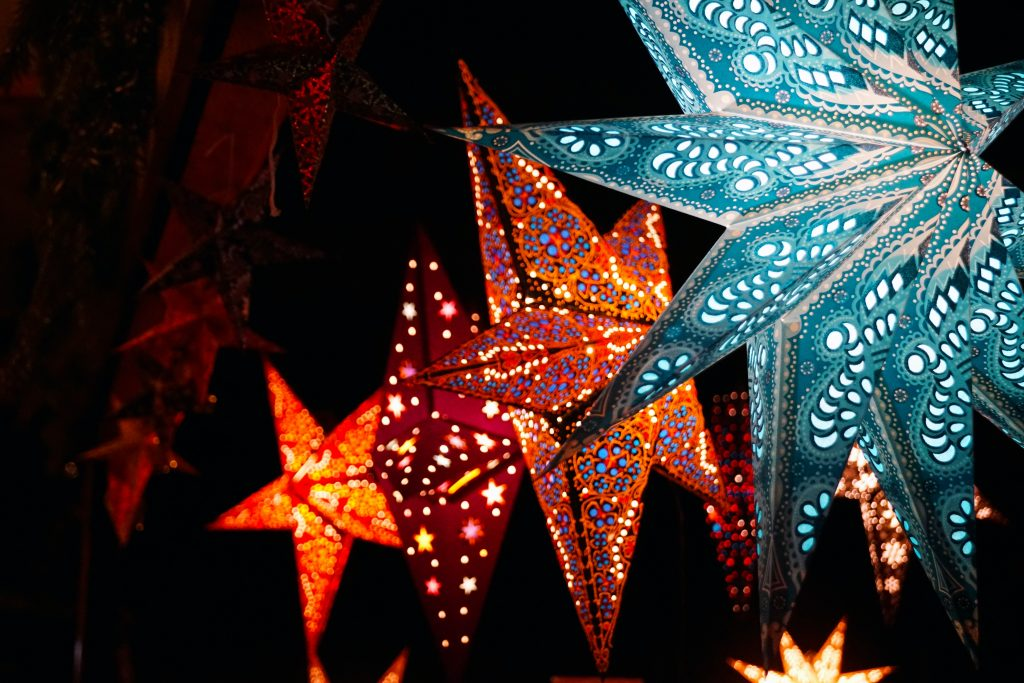 4 parols in blue and red christmas lights and dark sky background