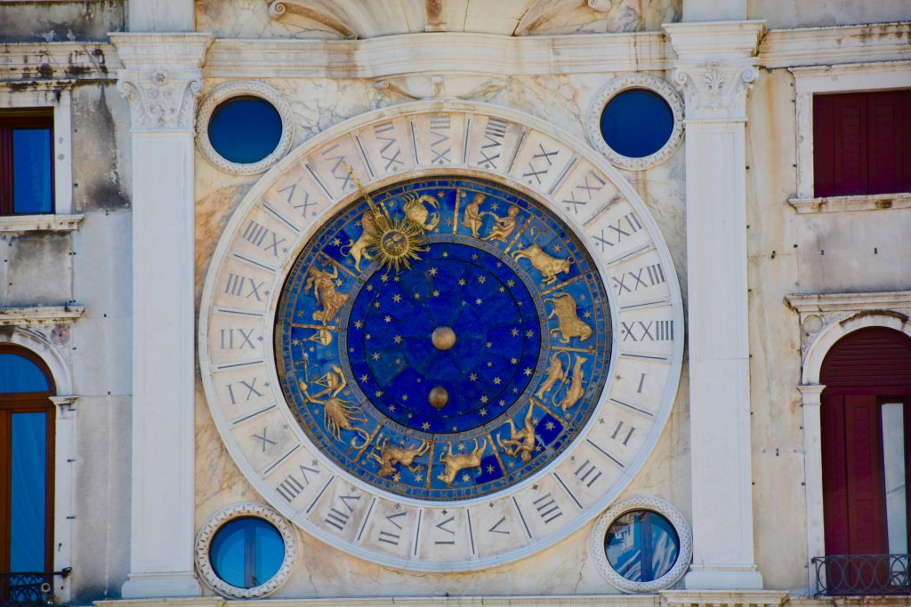 horoscope circle clock in yellow and blue hung on a building wall