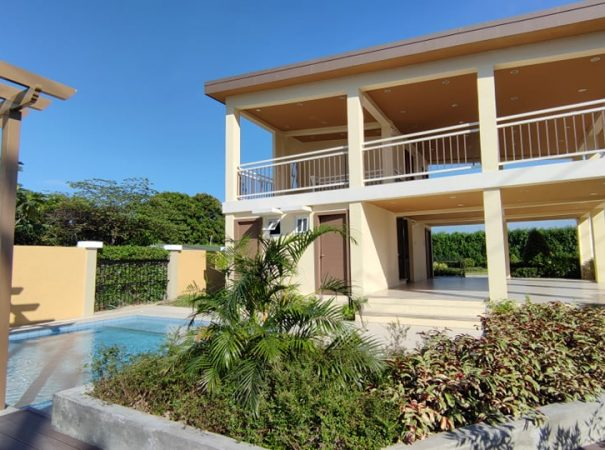 clubhouse and swimming pool amenities surrounded by green landscape with clear blue sky in Sevilla building condo for sale development in Las Pinas beside The Hermosa COHO