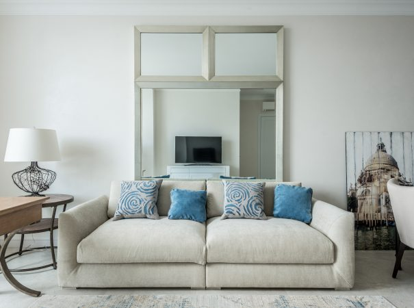 condo interior design of a living room space with off-white colored couch and blue pillows as accents to the motif and a wide tall mirror
